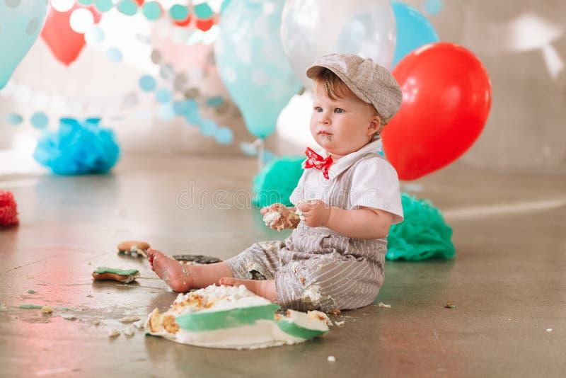 接触他的第一生日蛋糕的男婴 做杂乱cakesmash在装饰的演播室地点 肮脏的赤脚 图库摄影