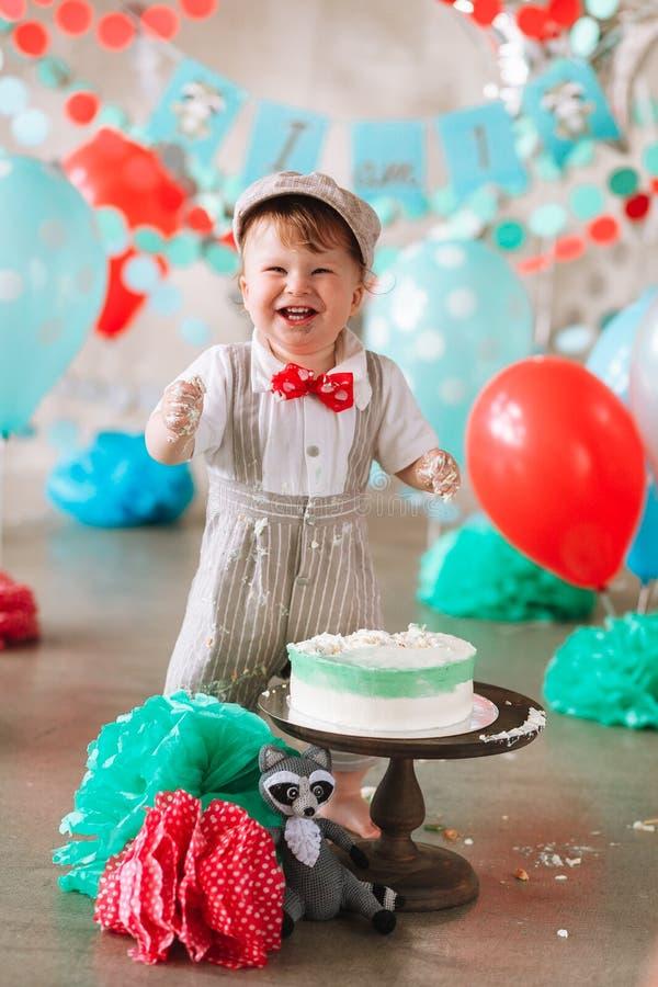 接触他的第一生日蛋糕的男婴 做杂乱cakesmash在装饰的演播室地点 库存图片