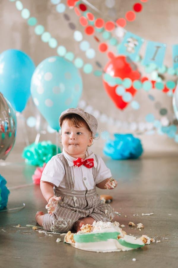接触他的第一生日蛋糕的男婴 做杂乱cakesmash在装饰的演播室地点 库存照片