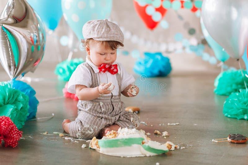 接触他的第一生日蛋糕的男婴 做杂乱cakesmash在装饰的演播室地点 免版税库存照片