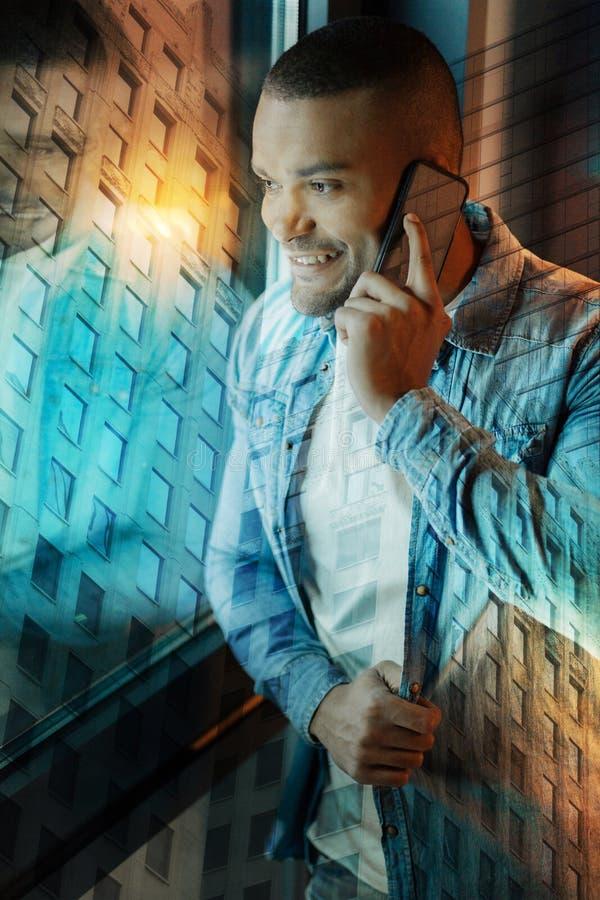 接触他的衬衣的激动的年轻人,当谈话在电话时 库存照片
