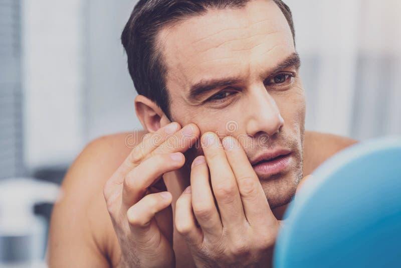 接触他的面孔的英俊的人,当看在镜子时 免版税库存图片