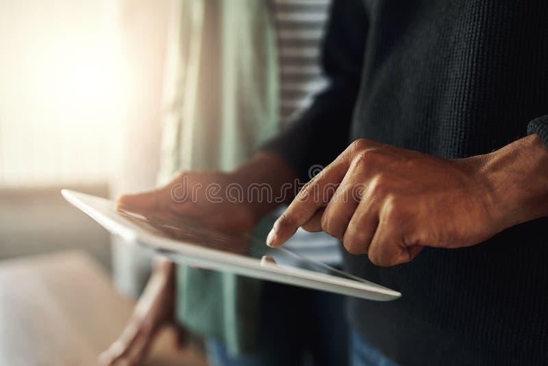 接触在数字片剂的一个人的特写镜头 图库摄影