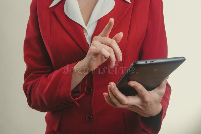 接触在片剂的红色夹克手指的企业女孩 图库摄影