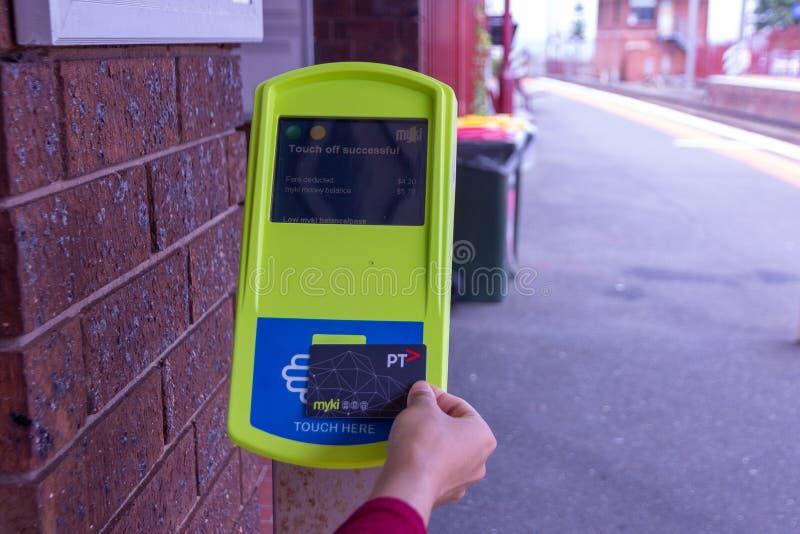 接触在myki卡片阅读机的通勤者在火车站平台 免版税图库摄影