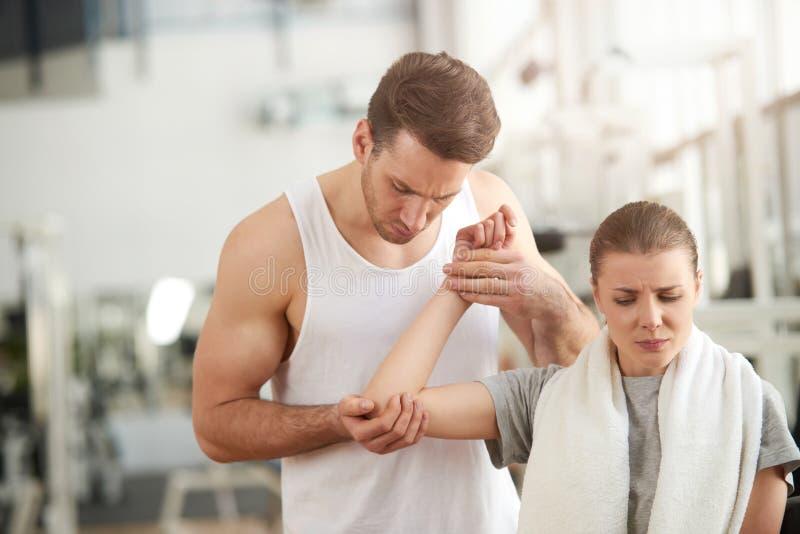 接触女性痛苦的手肘的人在健身房 免版税库存图片