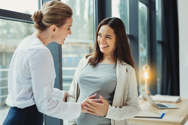 接触她怀孕同事和微笑的腹部的友好的秘书 库存照片