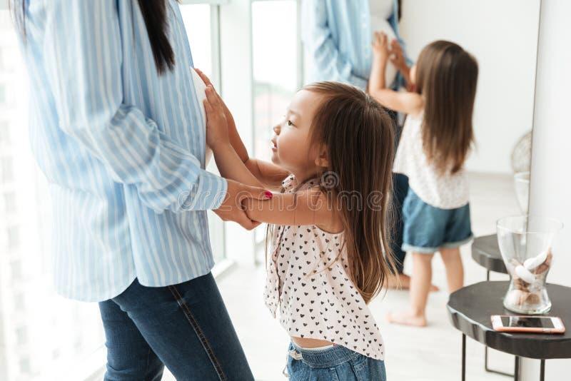 接触她怀孕的母亲的逗人喜爱的矮小的亚裔女孩鼓起 库存照片