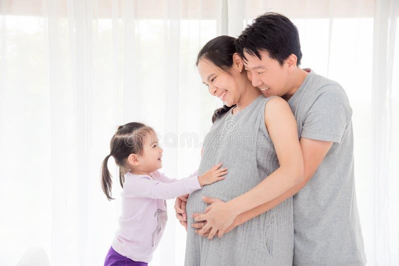 接触她怀孕的母亲腹部和微笑的女孩 免版税库存图片
