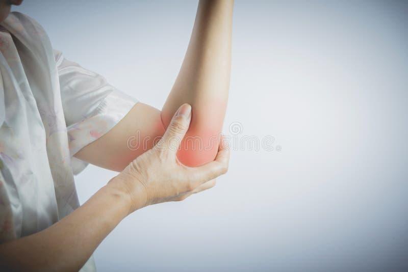 接触她痛苦的手肘的妇女 深刻手肘痛苦妇女 免版税库存照片