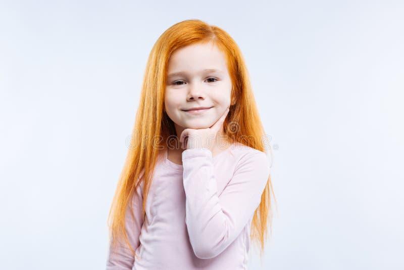 接触她的下巴的好快乐的逗人喜爱的女孩 免版税库存照片