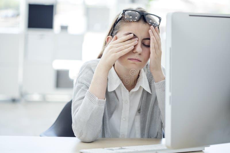 接触她的眼睛的疲乏的妇女 免版税库存照片