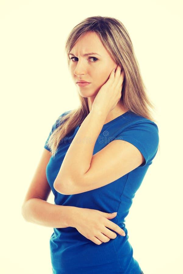 接触她的耳朵的年轻偶然妇女 库存图片