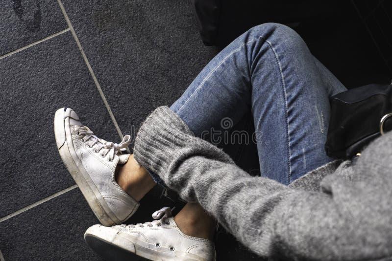 接触她的腿的妇女佩带的斜纹布和白色运动鞋,当坐地板时 免版税库存图片