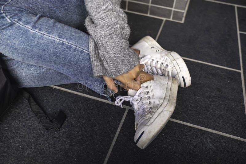 接触她的腿的妇女佩带的斜纹布和白色运动鞋,当坐地板时 免版税库存照片