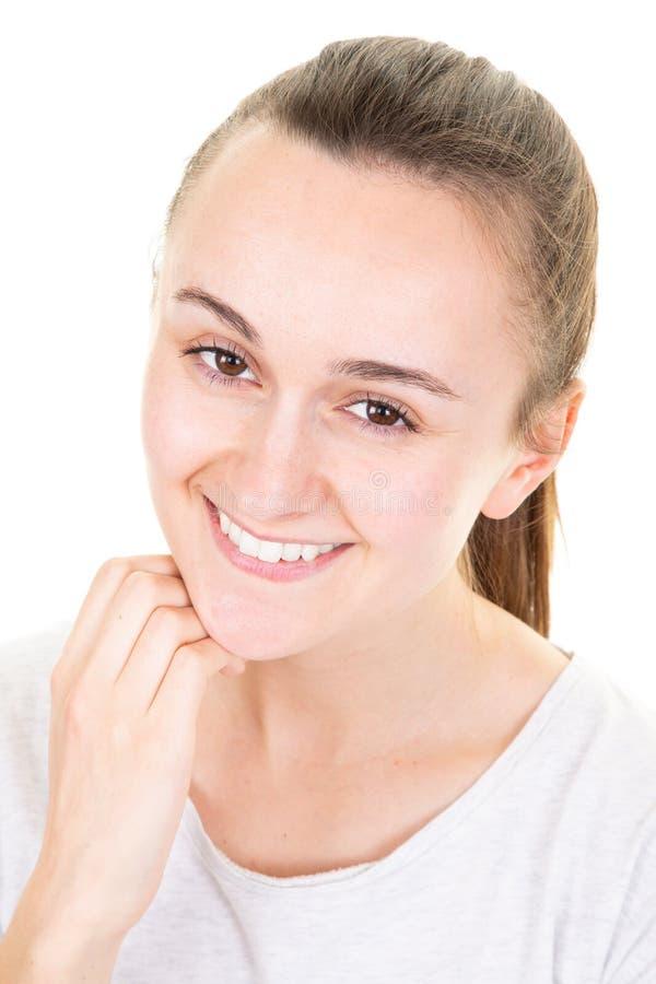 接触她的面孔的年轻微笑的妇女隔绝在白色背景 库存照片