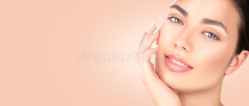 接触她的面孔的美丽的深色的女孩 完善的新鲜的皮肤 温泉秀丽画象 青年和skincare概念 库存照片