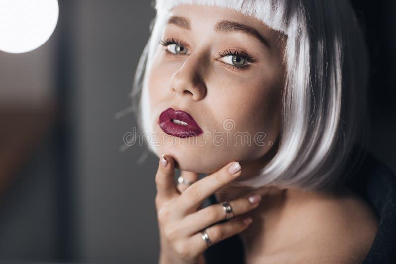 接触她的面孔的美丽的白肤金发的少妇 免版税图库摄影