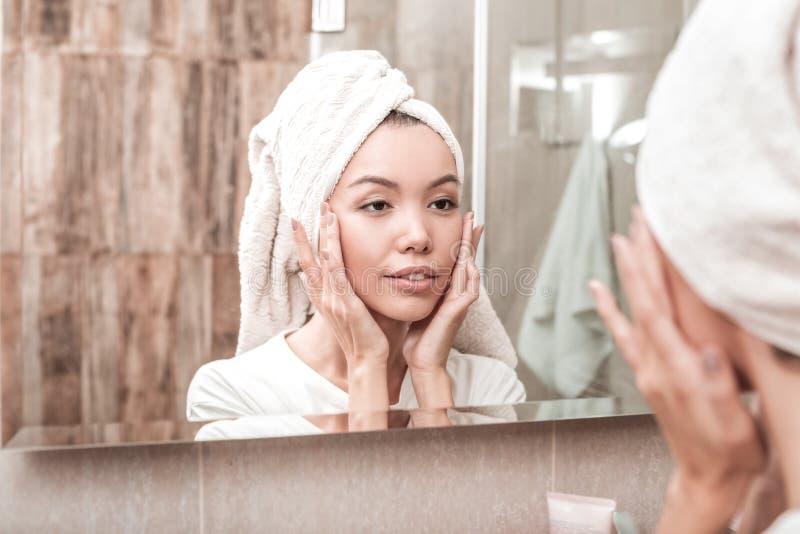 接触她的面颊的好年轻亚裔妇女 图库摄影