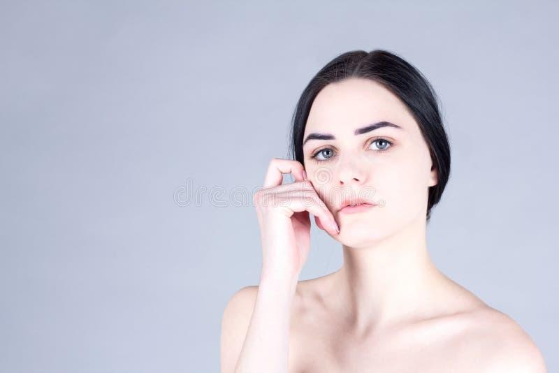接触她的面颊的赤裸妇女 免版税库存照片