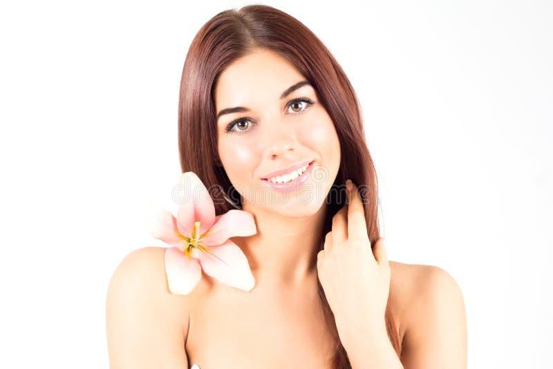 接触她的头发的美丽的温泉妇女 有桃红色花的妇女微笑与白色牙的 有新鲜和清楚的皮肤的妇女 库存照片