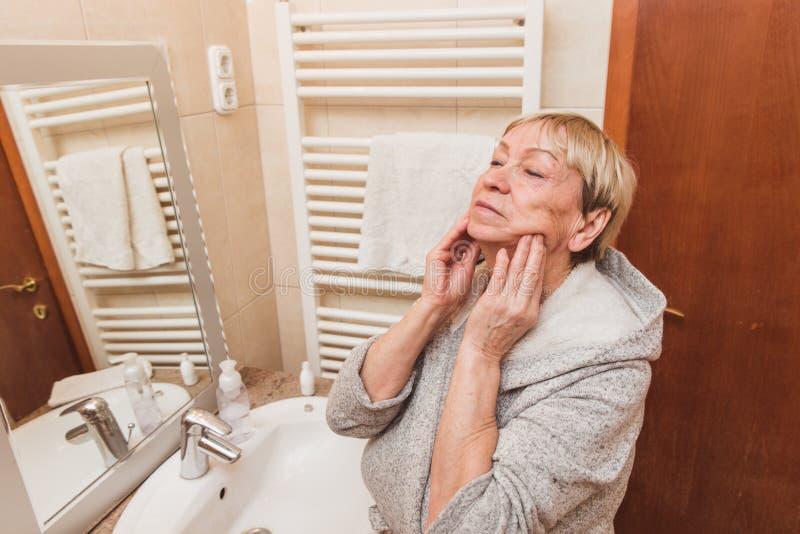 接触她软的面孔皮肤的资深妇女和做按摩,在家看在镜子 库存图片