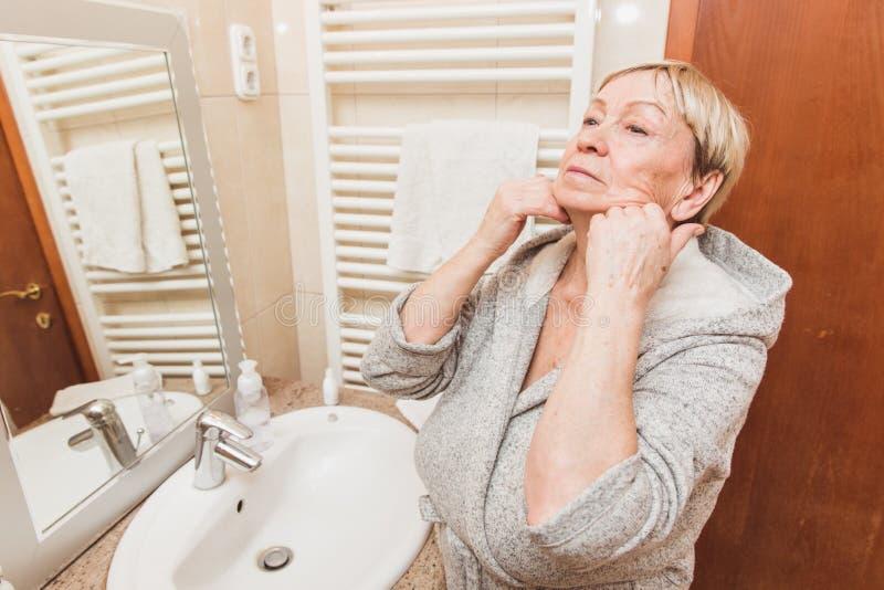 接触她软的面孔皮肤的资深妇女和做按摩,在家看在镜子 免版税库存照片
