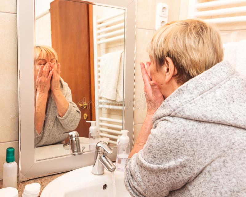 接触她软的面孔皮肤的资深妇女,在家看在镜子 免版税库存照片