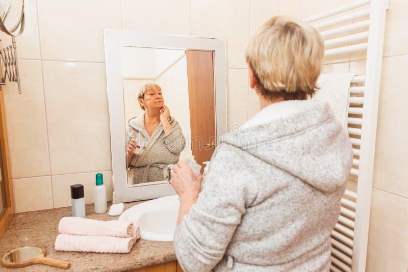 接触她软的面孔皮肤的资深妇女,在家看在镜子 免版税图库摄影
