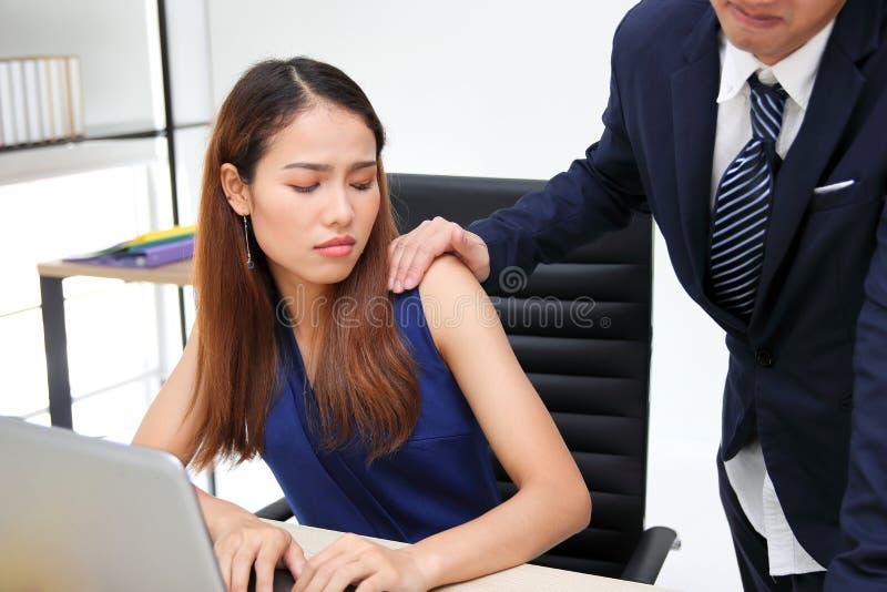 接触妇女肩膀的人上司在办公室工作场所  骚扰在办公室 免版税库存照片