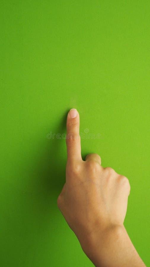 接触或指向在绿色屏幕上的人的手指 图库摄影
