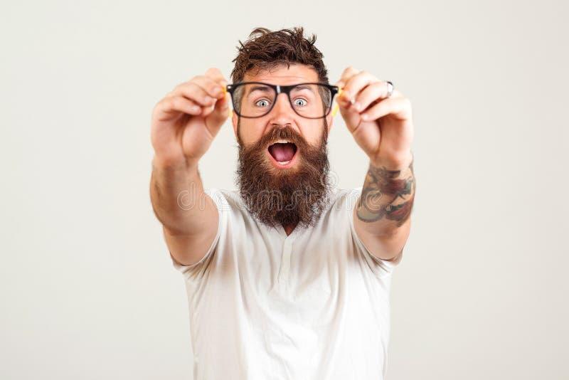 接触眼镜和保持他的嘴的激动的有胡子的人开放反对白色背景 有伟大的英俊的聪明的人 免版税库存照片