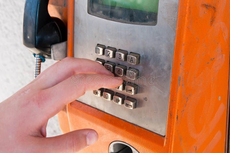 接触老未使用, unfunctional橙色公用电话的年轻男孩 免版税库存照片