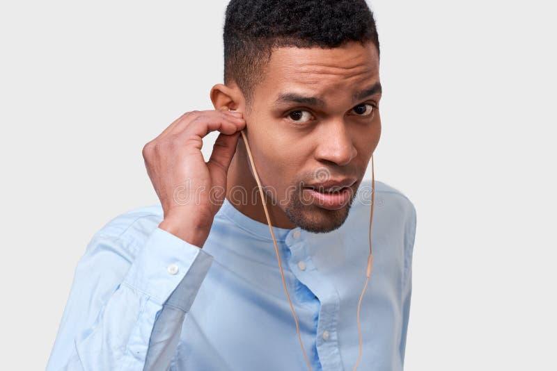 接触耳机的坦率的深色皮肤的人接近的演播室画象,听音乐 图库摄影