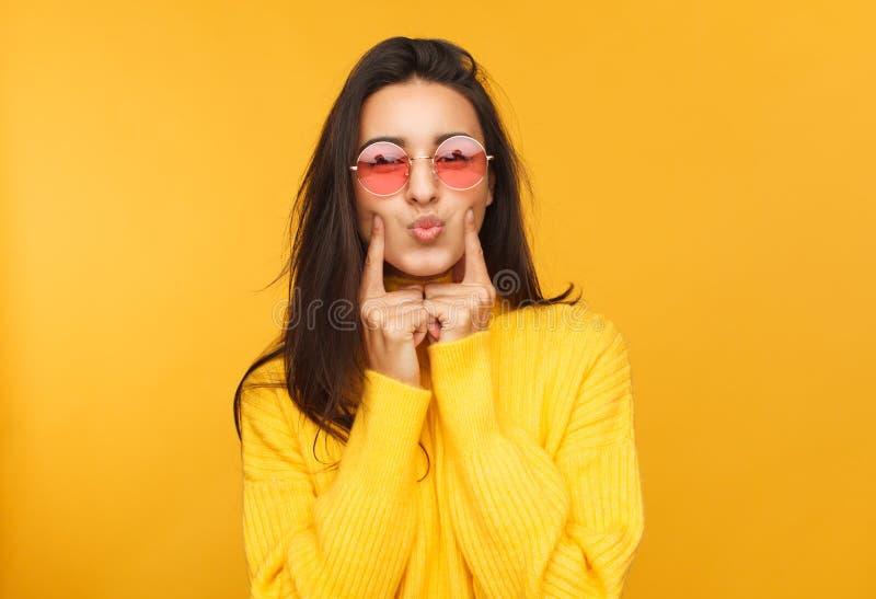 接触面颊的太阳镜的妇女 免版税库存照片