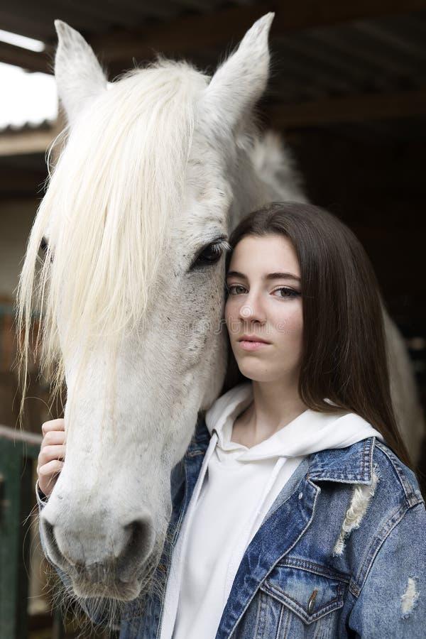 接触马的一个十几岁的女孩的画象 免版税图库摄影
