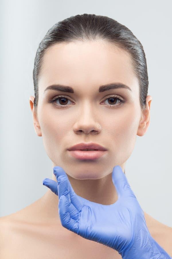接触年轻人的面孔橡胶手套的美容师 库存照片