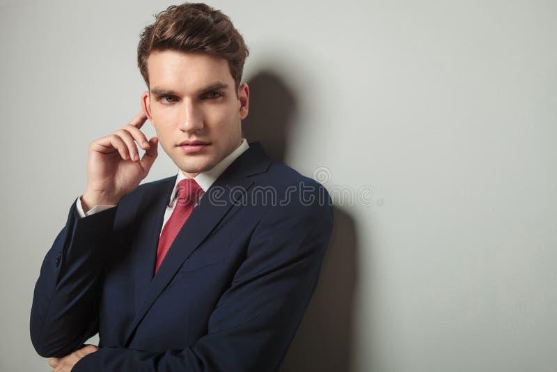 接触他的右耳朵的年轻商人 免版税图库摄影