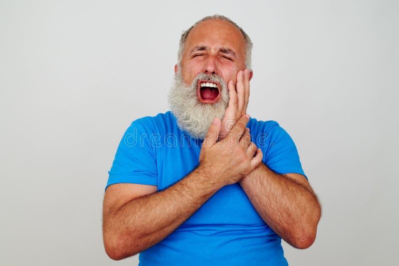 接触他的面颊的有胡子的人,好象有严厉牙痛 免版税库存照片