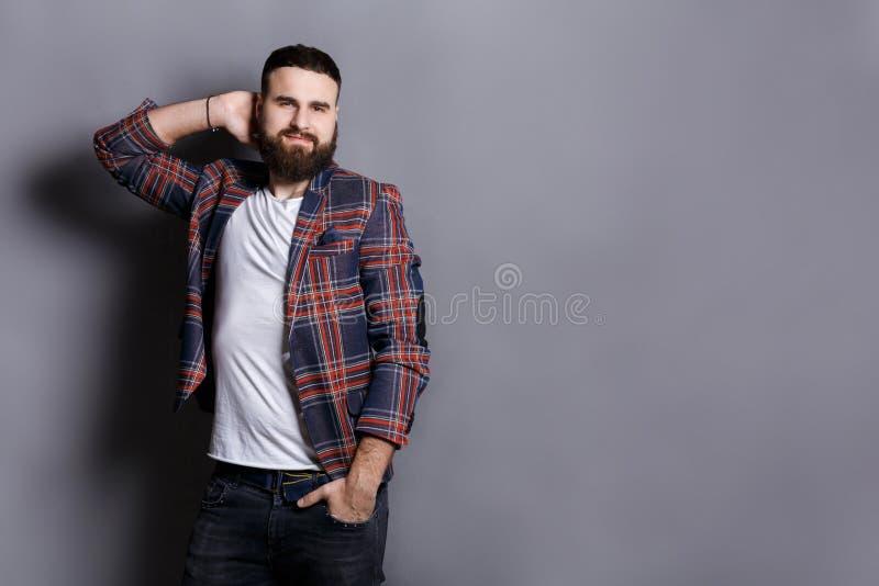 接触他的头发的英俊的有胡子的行家 免版税库存照片