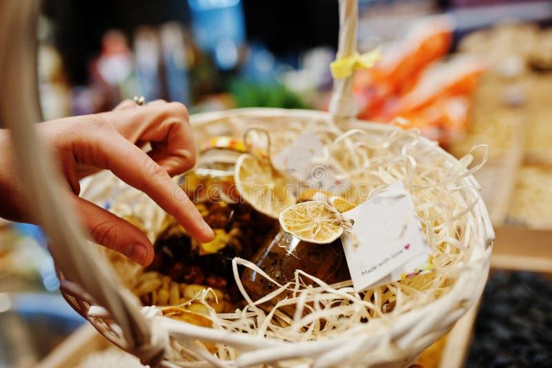接触hommemade瓶子用果酱的妇女的手在超级市场或杂货店的架子的篮子 做的爱 免版税库存照片