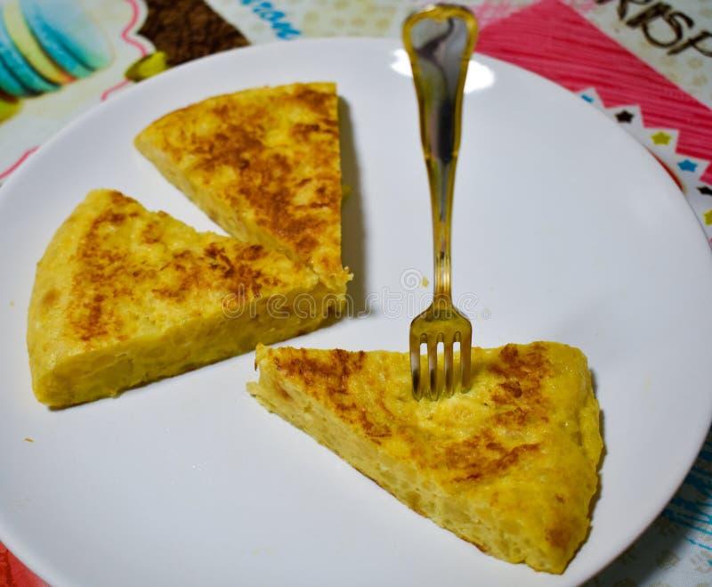 接近一个西班牙煎蛋的三个部分在一块白色板材的在桌的桌布 煎蛋卷的一个部分固定了  库存图片