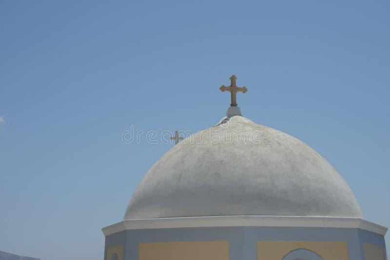 接近与一个典型的白色希腊教会的十字架的一个圆顶在Thira 免版税库存图片