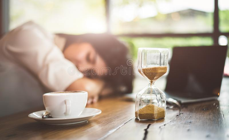 接近与女商人的sandglass疲乏从与手提电脑背景一起使用 放松睡觉和采取休息 免版税库存图片