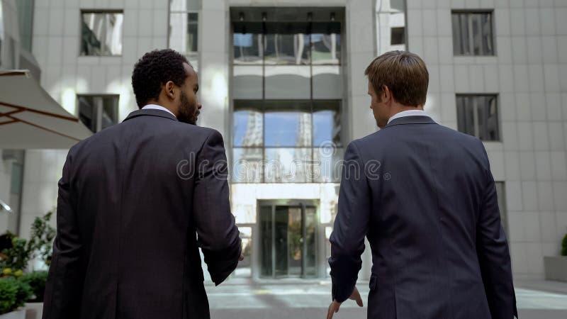 接近办公室中心的商务伙伴,谈论相互工作,合作 免版税库存照片