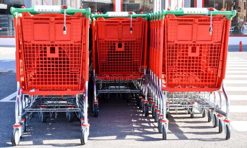 接近在几行整理的红色金属和塑料台车等待使用由买家在一个停车场在a 免版税库存图片