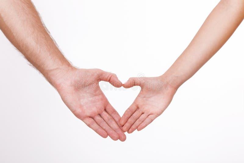 接近彼此的年轻夫妇和微笑做用他们的手指做的心脏形状被隔绝在白色背景 免版税库存图片