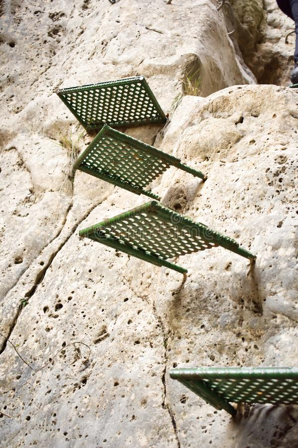 接近攀登山的墙壁的一块垂直的白色石头的一些绿色步帮助对徒步旅行者的保存空白得到 库存照片