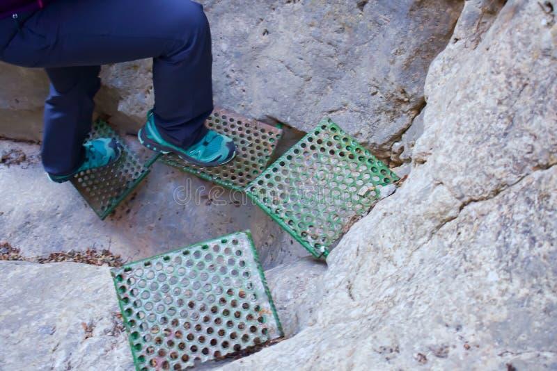 接近攀登山的墙壁的一块垂直的白色石头的一些绿色步帮助对徒步旅行者的保存空白得到 图库摄影