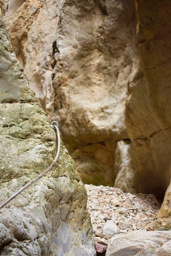 接近攀登山的墙壁的一块垂直的白色石头的金属串帮助对徒步旅行者的保存空白得到 免版税库存照片